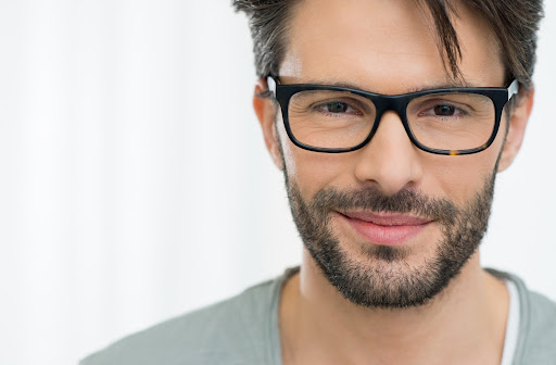 Handome man with dark eyes and short beard wearing perfectly fitting dark rimmed glasses staring straight into the camera