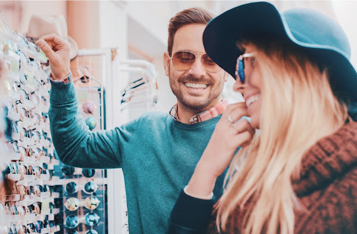 Young man and woman dressed fashionably and wearing sunglasses smiling at each other while browsing a wall of display glasses