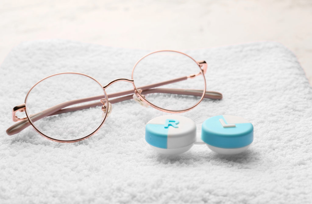 Glasses and contact lens box on white towel.